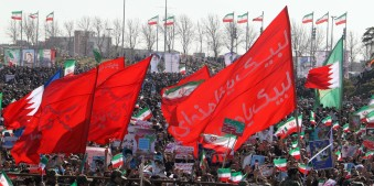 """Iranians wave religious banners and national flags of Iran and Bahrain during a rally to mark the 33rd anniversary of the Islamic revolution in Azadi (Freedom) square in Tehran on February 11, 2012. Iranian President Mahmoud Ahmadinejad said that Iran has broken the """"idol"""" of the Holocaust underpinning the creation of the Israeli state and US hegemony. AFP PHOTO/ATTA KENARE (Photo credit should read ATTA KENARE/AFP/Getty Images)"""
